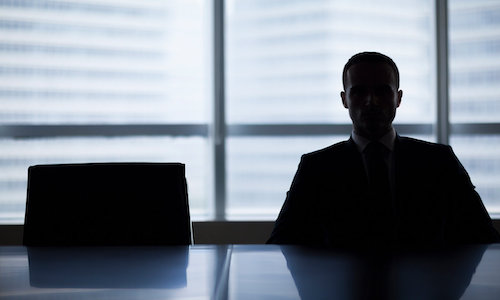 A silhouette of a man behind a desk.